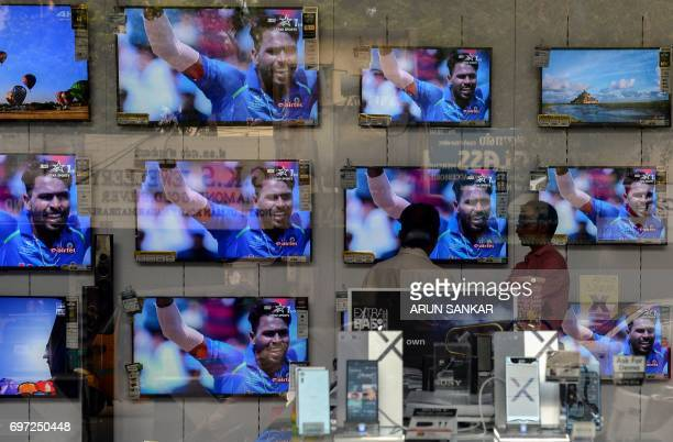 The IndiaPakistan cricket final match taking place in London is shown on televisions at an electronics showroom in Chennai on June 18 2017 The...