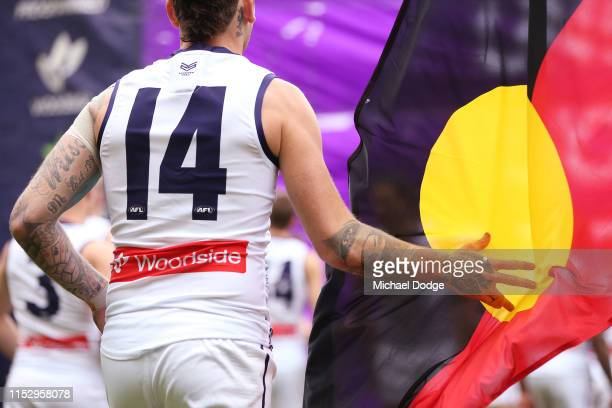 The Indigenous flag is seen as Dockers players run to the banner during the round 11 AFL match between the Collingwood Magpies and the Fremantle...