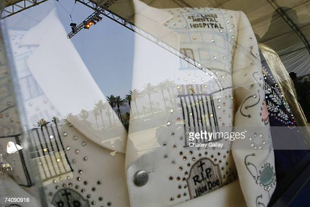 The Indio treeline is reflected off a glass case housing an original Nudie's cowboy suit at the Honky Tonk Museum in the Mustang Stage at the...