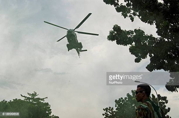 The Indonesian National Air Force slide down ropes that hang out of helicopters during a show to mark The Youth Pledge Day in Pekanbaru Indonesia on...