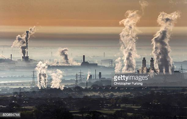 The industrial landscape across the Dee Estuary at sunrise as steam rises from Deeside power station Shotton Steelworks and other heavy industrial...