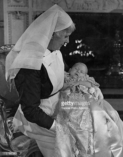 The infant Prince Charles in the arms of his nurse Sister Helen Rowe after his christening at Buckingham Palace London 18th December 1948