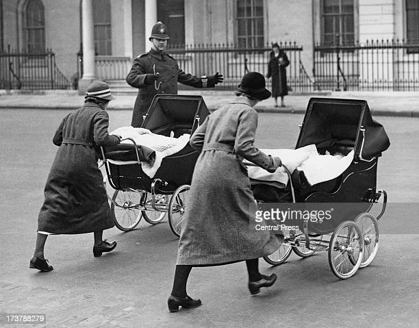 The infant Princess Alexandra of Kent and her brother, Prince Edward, Duke of Kent, with their nannies on an outing in their prams, 1937.