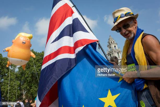 The inflatable balloon called Baby Trump flies above a Brexit protestor and the British Union Jack flag Parliament Square in Westminster the seat of...