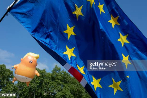 The inflatable balloon called Baby Trump flies above the European Union flag in Parliament Square in Westminster the seat of the UK Parliament during...