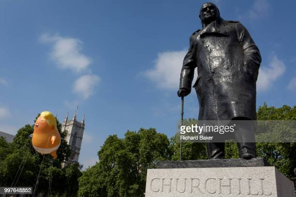 The inflatable balloon called Baby Trump flies above the statue of wartime Brish Prime Minister Winston Churchill in Parliament Square Westminster...