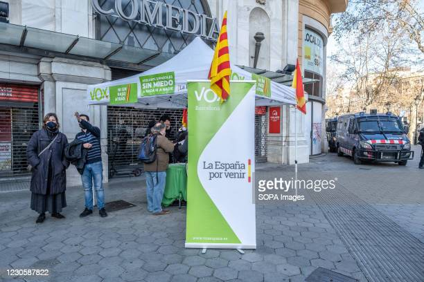 The information tent of the extreme right party VOX installed is seen set up in Passeig de Gràcia protected by agents of the Mossos d'esquadra....