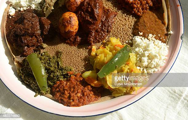 The injera an Ethiopian flat bread is set underneath a variety of traditional Ethiopian foods as Ethiopian families gather at a home in Aurora for a...