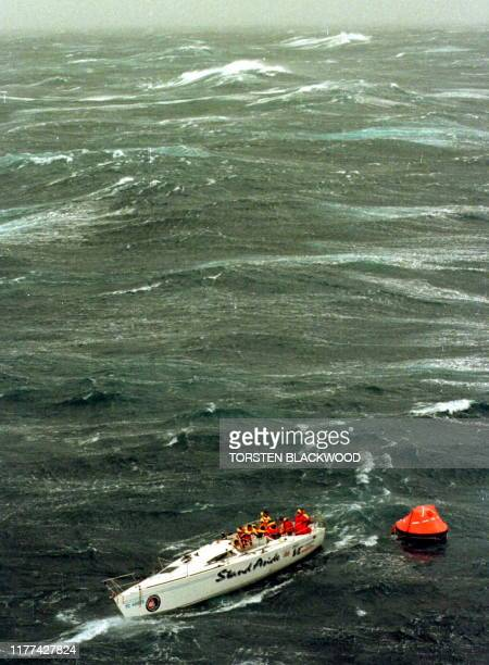 The injured crew of demasted Australian yacht Stand Aside await rescue by helicopter as they tow a liferaft in Bass Strait during the SydneytoHobart...