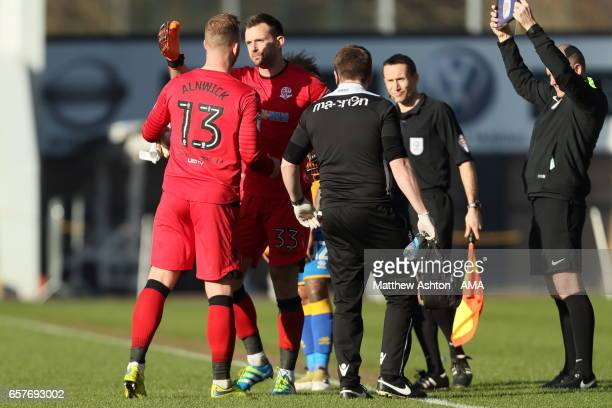 The injured goalkeeper Ben Alnwick is replaced by Mark Howard of Bolton Wanderers during the Sky Bet League One match between Shrewsbury Town and...