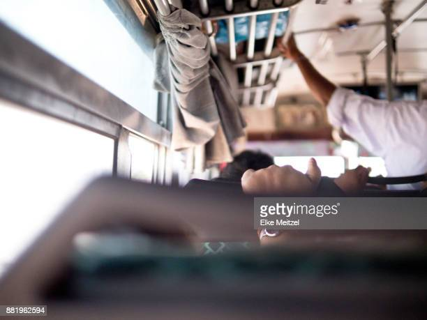 the inside of a local bus with hands holding onto rails photographed from the passenger point of view