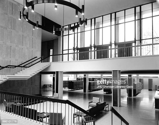 The inside of Milton S Eisenhower Library at its original design, including the open foyer and stairway between Q Level and M Level, with seating in...