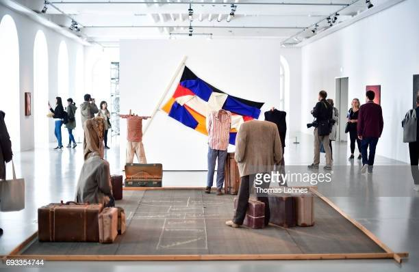 The installation 'Hopscotch' including six human figures nine suitcases metal bird cage and chalk on tarpaper by artist Vlassis Caniaris pictured on...