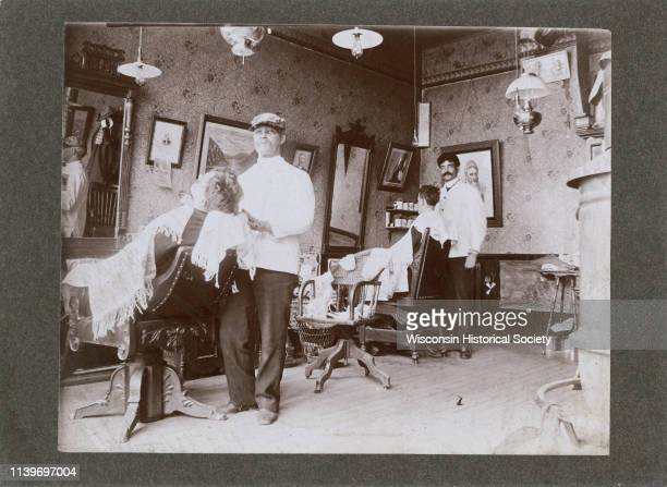 The interior of a barbershop with customers in chairs and barbers at work Black River Falls Wisconsin 1895 Numerous mirrors pictures and lamps are...