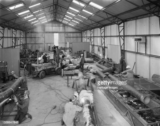 The interior of a large corrugated steel fabrication shop at the Bottesford pre-yield depot, showing workers cutting and welding pipework. In 1969,...