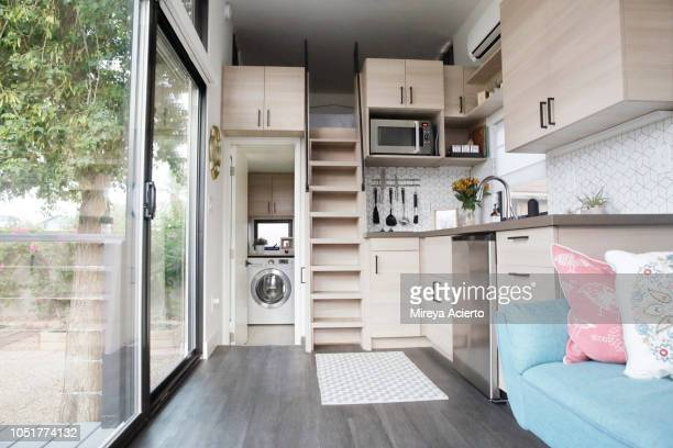 the interior of a tiny house with large glass windows, showcase the kitchen, living room and loft bedroom. - small stock pictures, royalty-free photos & images