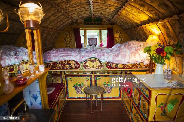 the interior of a traditional gypsy caravan with raised bed and cupboards, bow top roof and stove. - gypsy caravan stock pictures, royalty-free photos & images