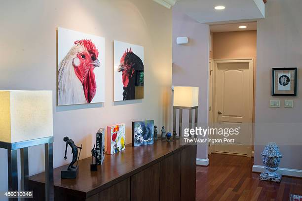 The interior of Greta De Keyser and Bart Vandaele's House feature's artwork with chickens hanging on their living room wall in Alexandria Virginia on...