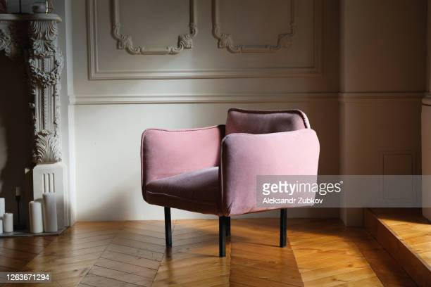 the interior of the living room is in english style with a pink velour chair against a light wall, with a wooden floor or parquet. - chair stock pictures, royalty-free photos & images