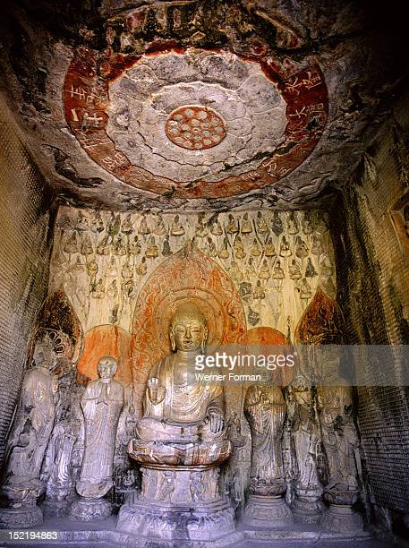 The interior of the Wanfo or Thousand Buddha cave at the Longmen cave temples The central figure portrays the Amitabha Buddha flanked by the monks...