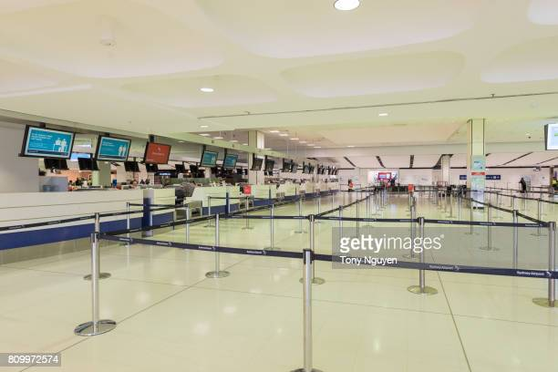 Sydney, Australia - June 13, 2017: The interiors of Sydney International Airport, departure area in a sunny day. Crew is waiting for clients to check in the luggage