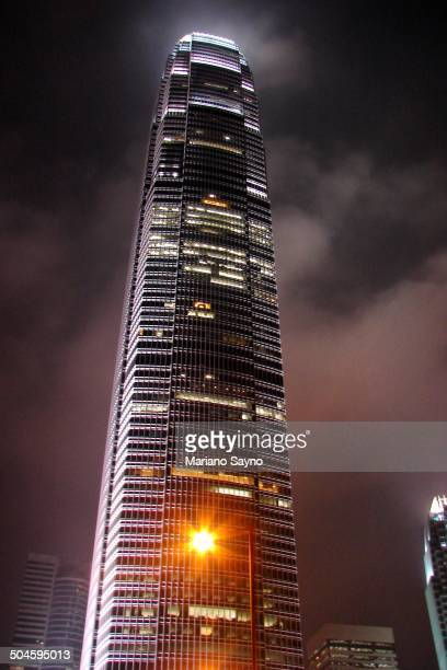 The International Finance Centre in Hong Kong , the 8th tallest skyscraper in the world, glows brightly against the overcast night sky.