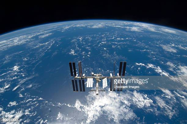 the international space station backdropped by a blue and white earth. - international space station stock pictures, royalty-free photos & images