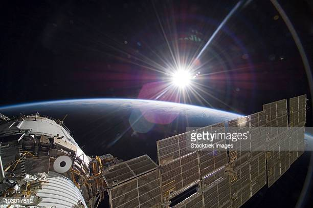 the international space station backdropped by the bright sun over earth's horizon. - space station stock photos and pictures