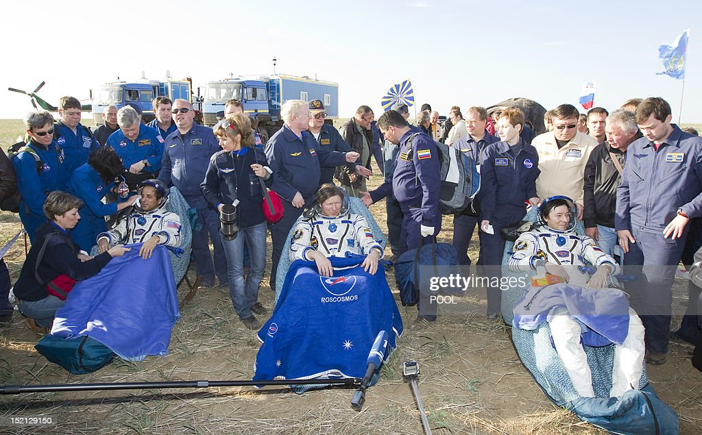 The International Space Station (ISS) crewmembers, US astronaut Joseph Acaba (L) and Russian cosmonauts Gennady Padalka (C) and Sergei Revin, rest shortly after the landing near the town of Arkalyk in northern Kazakhstan, on September 17, 2012. A woman took today command of the ISS for only the second time as three US and Russian colleagues made a safe return from the orbiting space lab to the Kazakh steppe.