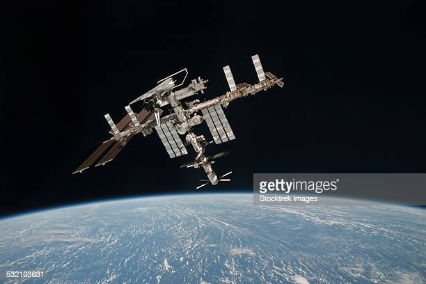 the international space station in orbit above earth. - international space station fotografías e imágenes de stock