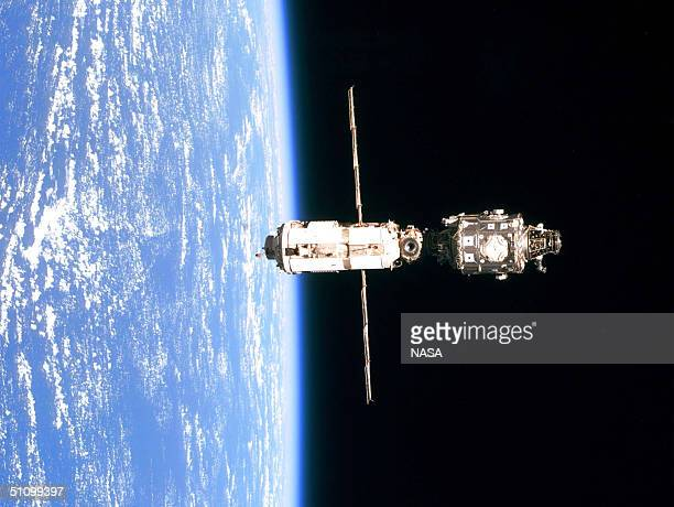 The International Space Station Is Backdropped Against The Blue And White Horizon Scene Of Earth And The Blackness Of Space Following Separation From...