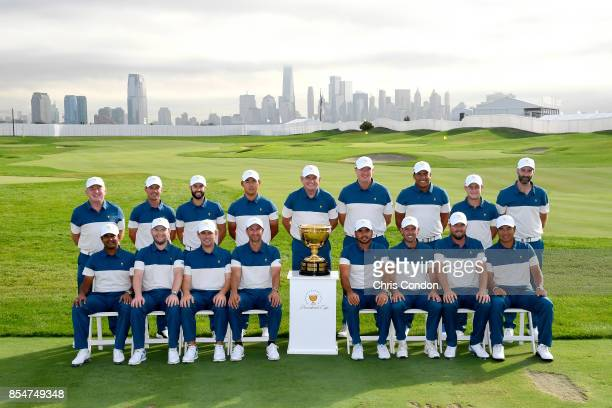The International Team poses for a group photo with the Presidents Cup trophy prior to the start of the Presidents Cup at Liberty National Golf Club...