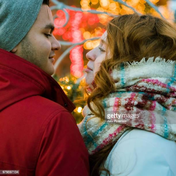 Interracial Liebespaar, Teenager, der schönen kaukasische Weiße langhaarige Mädchen 17 Jahre alt und gut aussehend Latino Hispanic 18 jährige junge, Weihnachtsbeleuchtung beobachten und Spaß in den kalten Wintertag in Brooklyn, New York