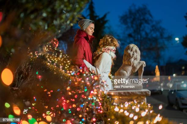 Interracial Liebespaar, Teenager, der schönen kaukasische Weiße langhaarige Mädchen 17 Jahre alt und gut aussehend Latino Hispanic 18 Jahre alte Junge, Umarmungen, umgeben von Weihnachtsbeleuchtung und Spaß in den kalten Wintertag in Brooklyn, New York