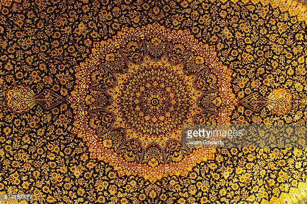 The intricate detail of a golden yellow Persian carpet.