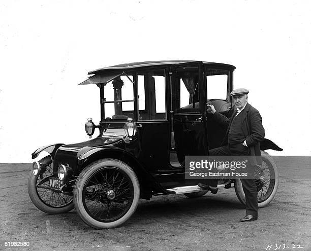 The inventor Thomas Alva Edison standing beside a Detroit Electric touring automobile produced by Detroit's Anderson Electric Car Company United...
