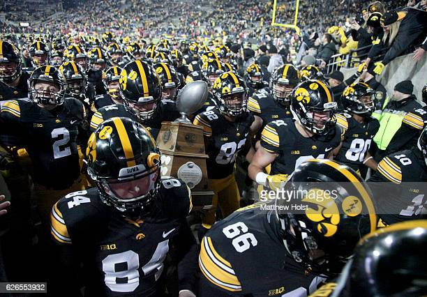 The Iowa Hawkeyes carry the Heroes Trophy off the field after defeating the Nebraska Cornhuskers on November 25 2016 at Kinnick Stadium in Iowa City...