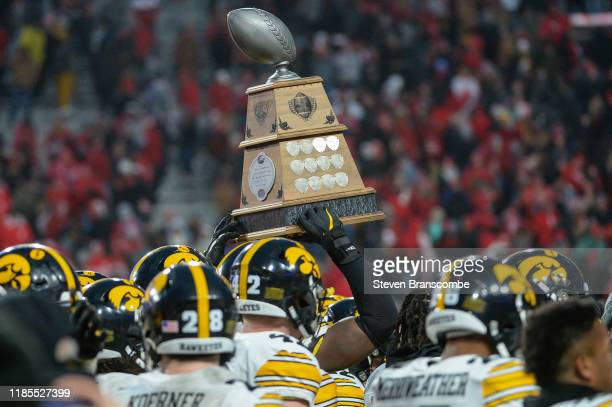 The Iowa Hawkeyes carry the Heroes Trophy off the field after the win against the Nebraska Cornhuskers at Memorial Stadium on November 29 2019 in...