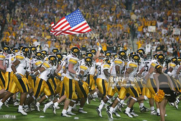 The Iowa Hawkeyes take the field against USC as a team member holds the United States flag before the FedEx Orange Bowl on January 2 2003 at Pro...