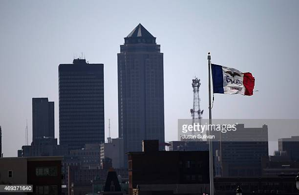 The Iowa state flag flies in front of the Des Moines skyline on April 11 2015 in Des Moines Iowa Former secretary of state Hillary Clinton is...