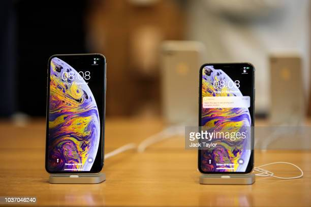 A customer purchases iPhones and an Apple Watch at the Apple Regent Street store during the launch of the iPhone XS on September 21 2018 in London...