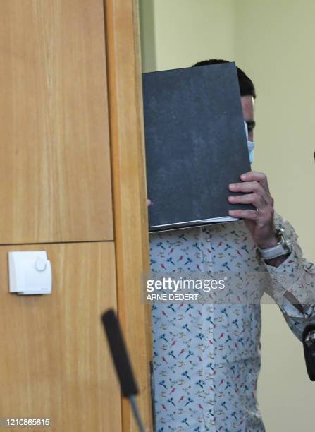 The Iraqi defendant identified only as Taha alJ believed to have belonged to the Islamic State jihadist group hides his face before the start of his...