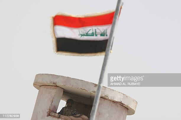 The Iraqi flag flutters in front of an Iraqi policeman standing guard as a street is reopened in the Saidiya neighborhood of southern Baghdad on...
