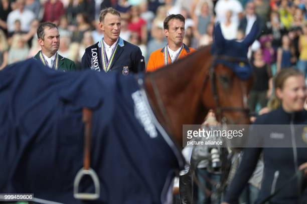 The Irish show jumper Cian O'Connor Sweden's Peder Fredricson and the Netherland's Harrie Smolders stand on the podium after the single show jumping...