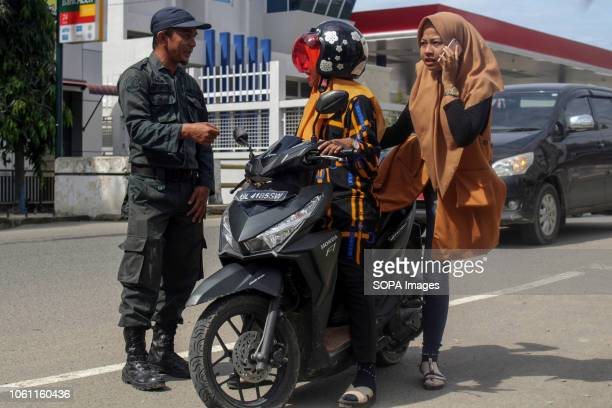 LHOKSEUMAWE ACEH INDONESIA The Islamic Sharia Police officer seen stopping a motorist wearing tight clothes during the routine raids in Lhokseumawe...
