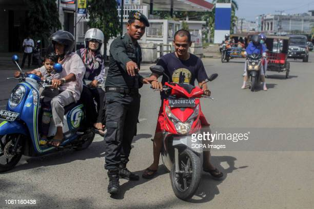 LHOKSEUMAWE ACEH INDONESIA The Islamic Sharia Police officer seen stopping a motorist wearing shorts during the routine raids in Lhokseumawe Islamic...