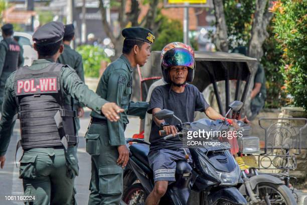 LHOKSEUMAWE ACEH INDONESIA The Islamic Sharia Police officers are seen stopping a motorist wearing shorts during the routine raids in Lhokseumawe...