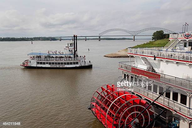 The Island Queen riverboat moves past the Queen of the Mississippi docked at Beale Street Landing in Memphis Tennessee US on Monday Aug 18 2014 The...