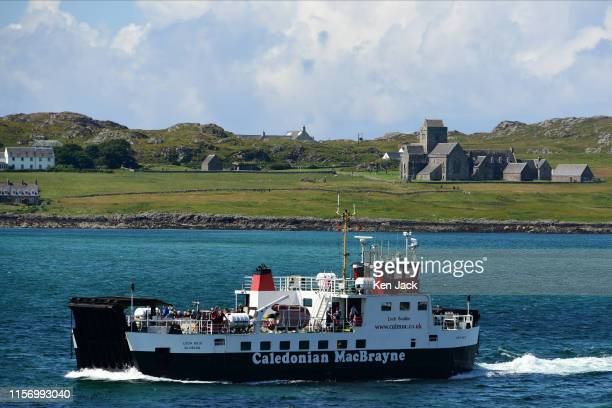 The Isle of Mull to Iona ferry passes in front of the world famous Iona Abbey in bright sunshine, on July 20, 2019 in Fionnphort, Scotland. The Abbey...
