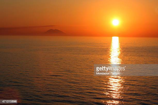 The isle of Stromboli seen beyond the sea from the beach of Marina dell'Isola at sunset in a photo shooting Tropea Italy April 2005